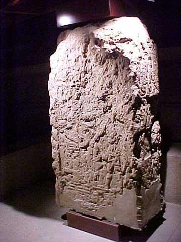 Estela de arenisca del periodo grecorromano encontrada entre los escombros de la capilla de Adijalamani.  En la parte inferior una escena de un rey ante una divinidad sentada, cuya corona es similar a la de los dioses Shu-Aresnufis, o Thot de Pnubs o del propio Amón. Como protectores, una serpiente ondulante y un león sentado