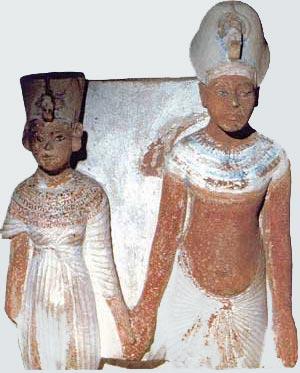 Fig. 6. Estatuilla doble en caliza pintada de Akhenaton y Nefertiti, que la forma del nombre Atón de la parte posterior permite datar en fecha no anterior al año 9. Hay cierta ingenuidad en la escultura que todavía sigue los cánones establecidos según los cuales la reina debía aparecer a menor escala. Museo del Louvre.
