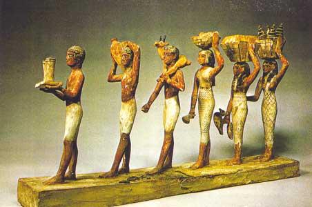 Fig. 25 - Maquetas de Meketre. La tumba de Meketre, canciller de Mentuhotep I, estaba situada cerca de la tumba de su amo y, de acuerdo con los usos de la época, se construyó una rampa de acceso muy inclinada y una enorme entrada con un pasillo que se adentra en el acantilado. A pesar de que en la antigüedad la tumba había sido fuertemente saqueada y destrozada, en las investigaciones dirigidas por Herbert Winlock en 1919-1920 se encontró una pequeña cámara oculta que contenía las 25 maquetas de madera con escenas de la vida cotidiana que han sobrevivido. Elescondite contenía una maqueta del recuento del ganado, dos mujeres portadoras de ofrendas, maquetas de carnicerías y panaderías, géneros, tejedurías y carpinterías, esquifes de pesca y la flotilla del gran hombre
