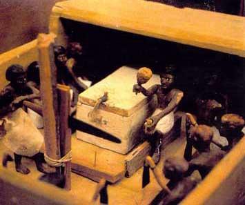 Fig. 25 y 26. Maquetas de Meketre. La tumba de Meketre, canciller de Mentuhotep I, estaba situada cerca de la tumba de su amo y, de acuerdo con los usos de la época, se construyó una rampa de acceso muy inclinada y una enorme entrada con un pasillo que se adentra en el acantilado. A pesar de que en la antigüedad la tumba había sido fuertemente saqueada y destrozada, en las investigaciones dirigidas por Herbert Winlock en 1919-1920 se encontró una pequeña cámara oculta que contenía las 25 maquetas de madera con escenas de la vida cotidiana que han sobrevivido. Elescondite contenía una maqueta del recuento del ganado, dos mujeres portadoras de ofrendas, maquetas de carnicerías y panaderías, géneros, tejedurías y carpinterías, esquifes de pesca y la flotilla del gran hombre.