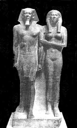Fig. 51. Micerinos y su reina Jamerarnebty. Obsérvese la manera en que ella rodea a su esposo con el brazo derecho y apoya el izquierdo de él. Estatua de pizarra. Museo de Boston.