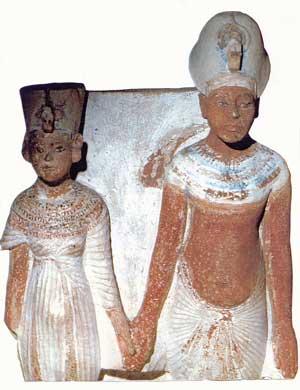 Fig. 66. Estatuilla doble en caliza pintada de Akhenaton y Nefertiti, que la forma del nombre Atón de la parte posterior permite datar en fecha no anterior al año 9. Hay cierta ingenuidad en la escultura que todavía sigue los cánones establecidos según los cuales la reina debía aparecer a menor escala. Museo del Louvre.