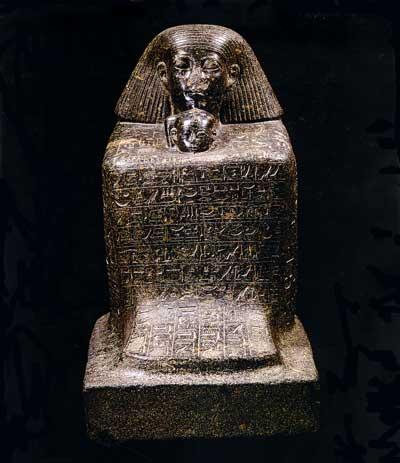 Fig. 82. Senmut, canciller y preceptor de la princesa Neferure (con trenza y ureo) en una estatua-cubo de granito. Museo de Berlín.