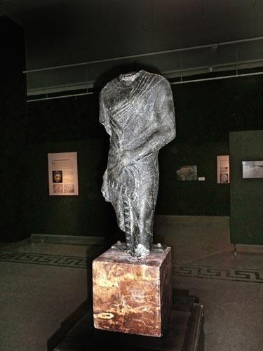 Fig. 3. Escultura de basalto negro representando la figura de un funcionario de época ptolemaica hallada en Alejandría, s. II-I a.C. (colección MAC-Barcelona). Oxirrinco, junto con Alejandría, era una de las dos principales colonias griegas durante el reinado de los Ptolomeos.