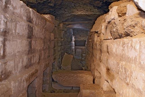 Fig. 18. Galería núm.1 con nichos de época ptolemaica. El pasadizo, cubierto con grandes losas, está flanqueado a ambos lados por veintiocho nichos de idénticas dimensiones. La mayoría presenta en el dintel una inscripción hierática en negro. En su interior se depositaban los simulacros del dios Osiris.