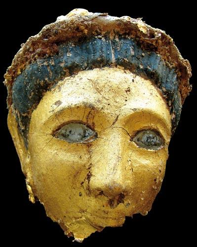 Fig. 22. Máscara dorada. En la sala norte de la tumba 5, entre los estratos de materiales de derribo se localizaron diferentes momias romanas, una de la cuales tiene un cartonaje dorado, y una máscara muy bien conservada, con una lámina de oro con incrustaciones de pasta de vidrio en los ojos. Una diadema adorna el elaborado peinado.
